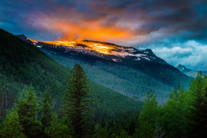 The rising sun breaks through the looming storm clouds to light up the snow atop Logan Pass in Glacier National Park in Montana. Part of the Darkroom Gallery Exhibit The Natural Realm.