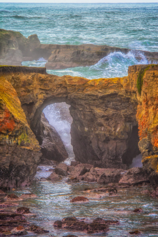 Waves crash against a sea arch located at Point Arena Lighthouse along California's northern coast, south of Mendocino.