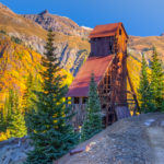 Morning light picks out features on the headframe of the Yankee Girl Mine near Ouray, CO, on Ouray County Road 31. In the distance aspens and scrub oal color the mountainside.