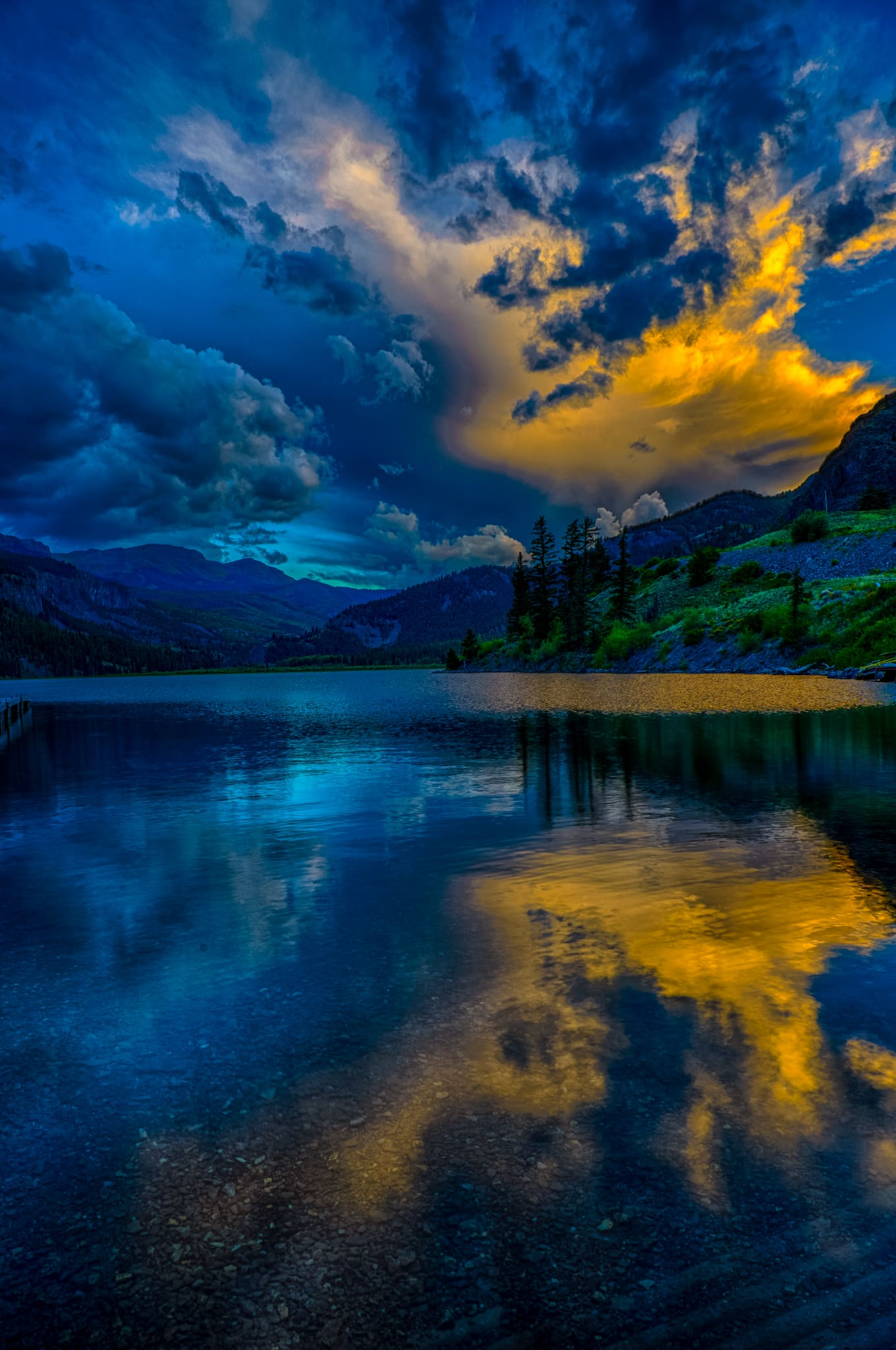The last light of sunset illuminating a cloud is reflected the the water of Lake San Cristobal near Lake City, Colorado.