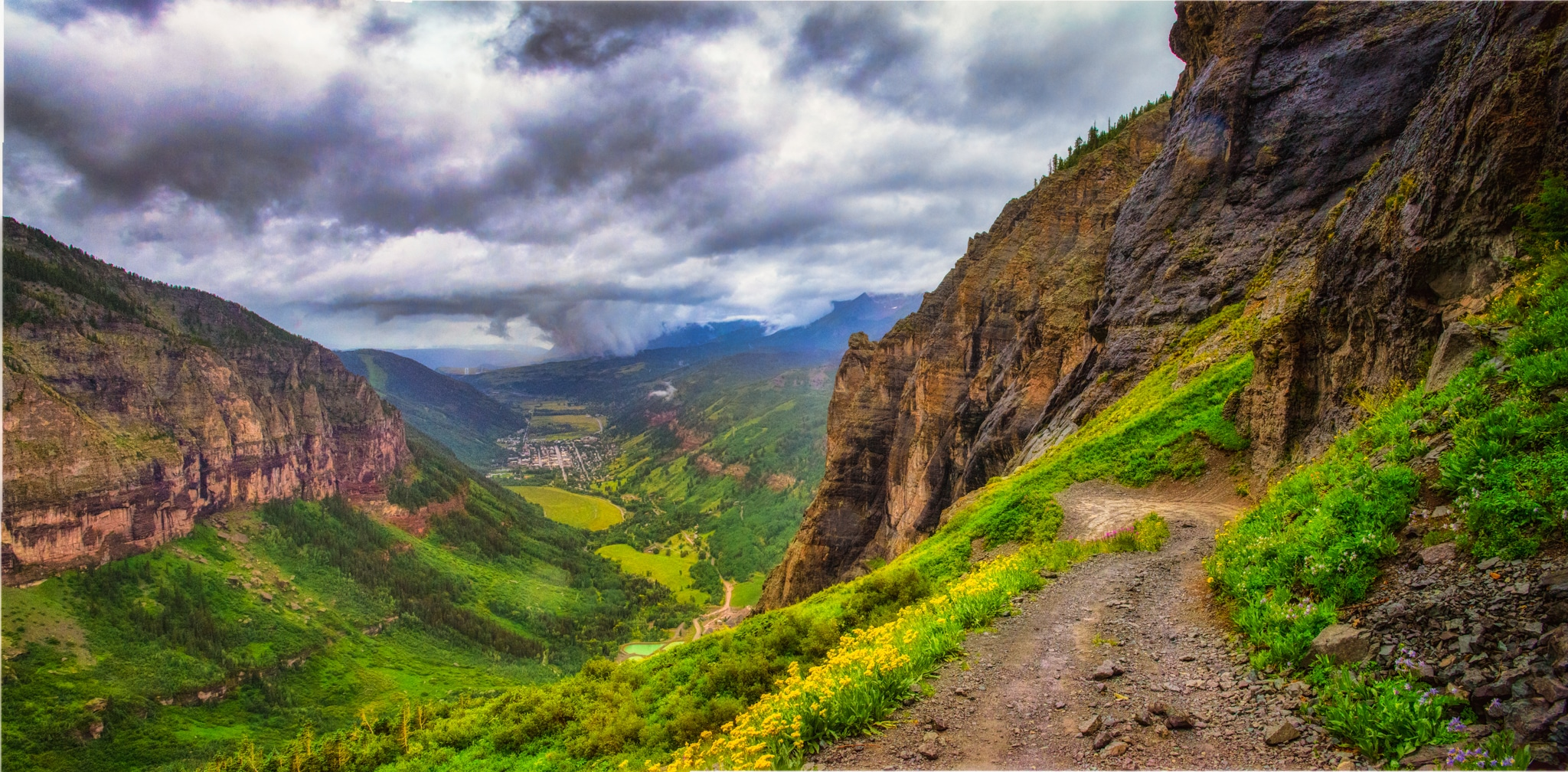 From a switchback on Black Bear Road, the town of Telluride, Colorado, becomes visible through the rain clouds and fog.