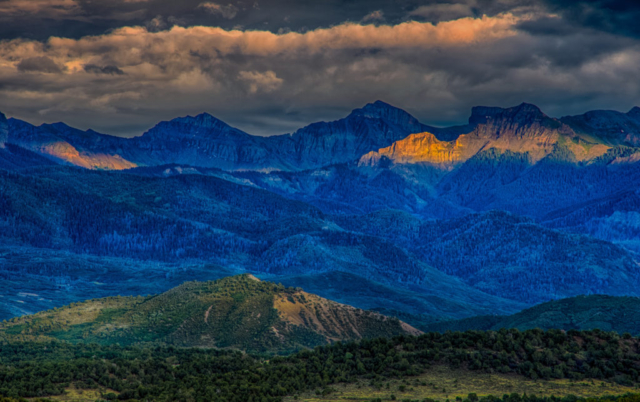 Late afternoon light escapes the heavy cloud cover to illuminate a portion of the Cimarron Mountains. Taken from Ridgway State Park near Ridgway, Colorado.
