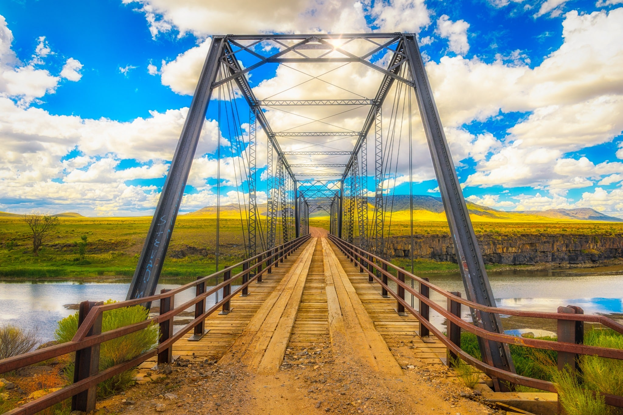 This is a view through the Lobato Bridge (Costillo Crossing Bridge) on the Rio Grande River, about 13 miles east of Antonito, Colorado, on Conejos County Road G. The Lobato Bridge is the southernmost bridge across the Rio Grande River in Colorado. This bridge is classified as a two-span Thacher through truss bridge.
