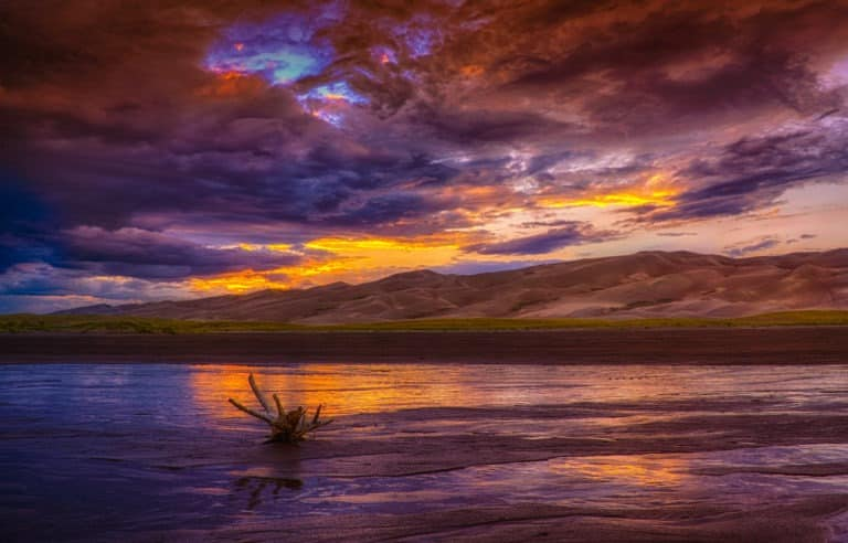 The last light of day highlights the driftwood in Medano Creek in Great Sand Dunes National Park and Preserve, near Alamosa, Colorado.
