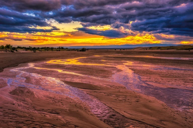 The last light of day turns the waters of Medano Creek gold in Great Sand Dunes National Park and Preserve, near Alamosa, Colorado.
