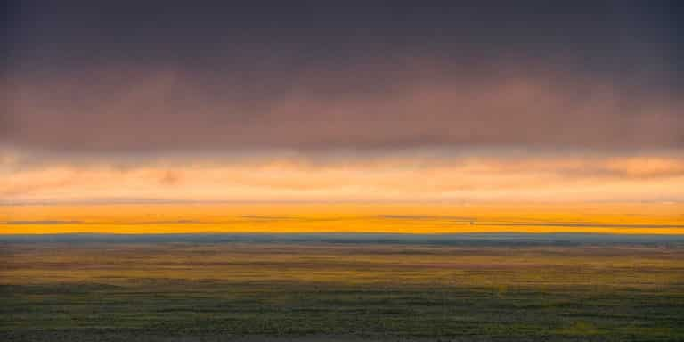 This panorama shows golden cloud cover shrouding the tops of the dunes on an early morning in September at Great Sand Dunes National Park and Preserve near Alamosa, Colorado.