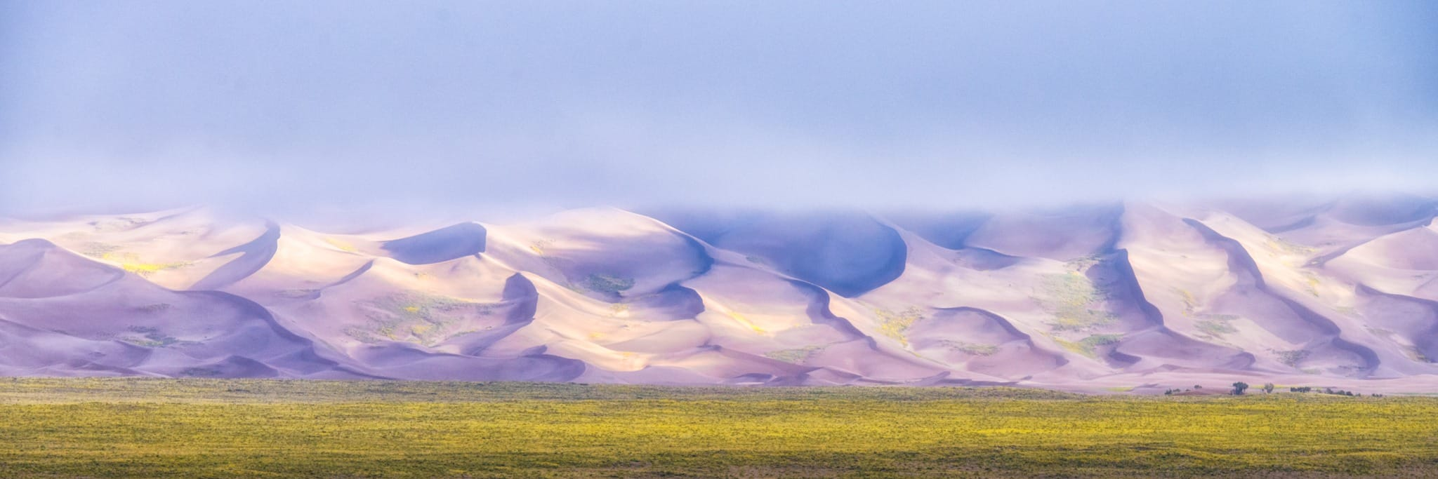 This panorama shows cloud cover shrouding the tops of the dunes on an early morning in September at Great Sand Dunes National Park and Preserve near Alamosa, Colorado.