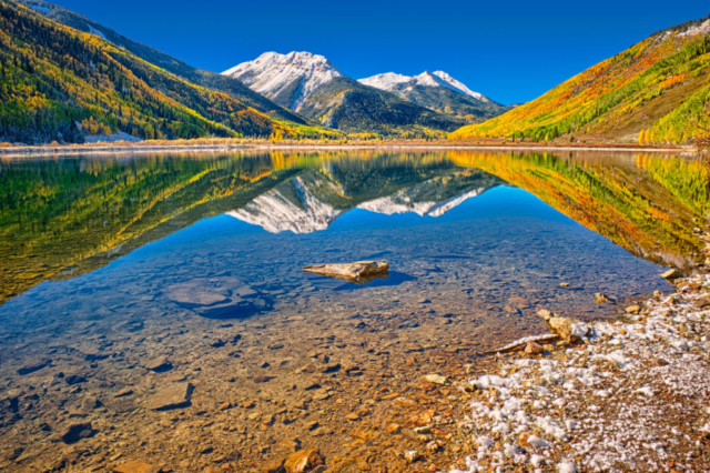 Snowy Red Mountain and autumn aspens are reflected in Crystal Lake, located on US 550 near Ironton, Colorado.