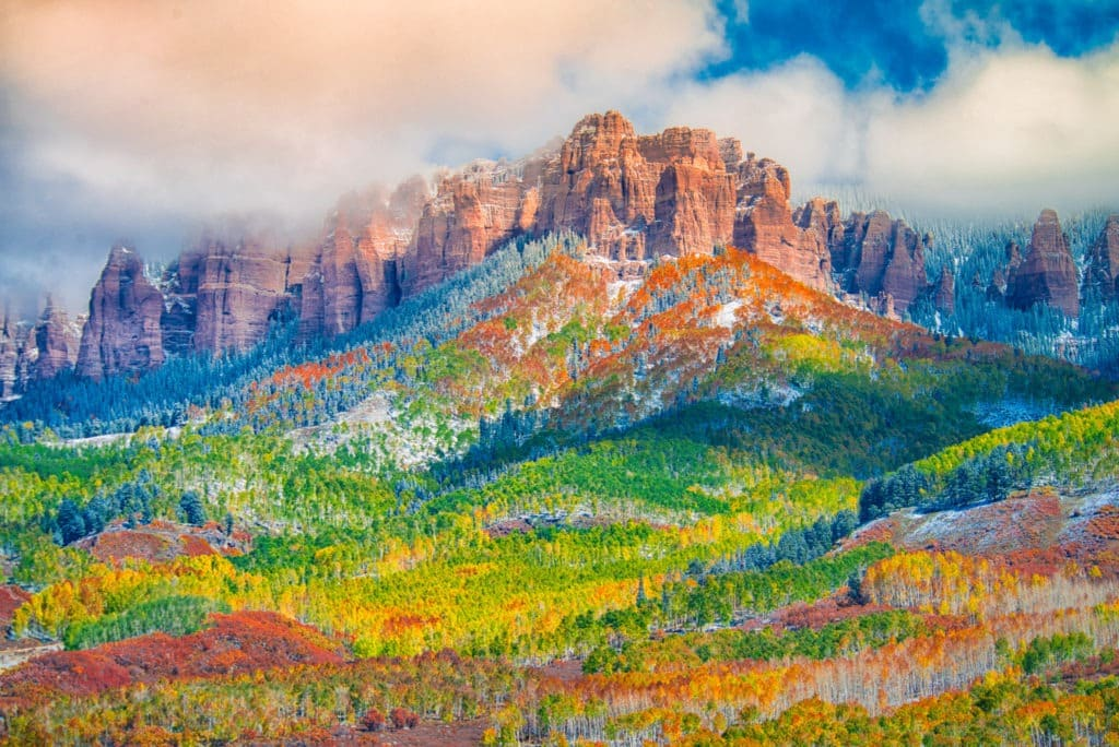 Russet oaks and golden aspens lead the eye up to the snowy Cimarron Mountains as seen from Owl Creek Pass Road near Ridgway, Colorado. It is one of the best fall color locations in the San Juan Mountains.