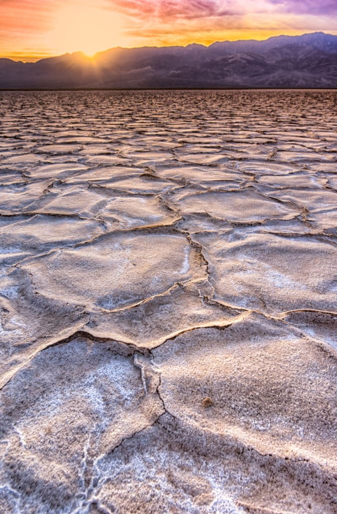 The low angle of the setting sun highlights the hexagonal plates of salt crystals in Badwater Basin in Death BValley National Park, California