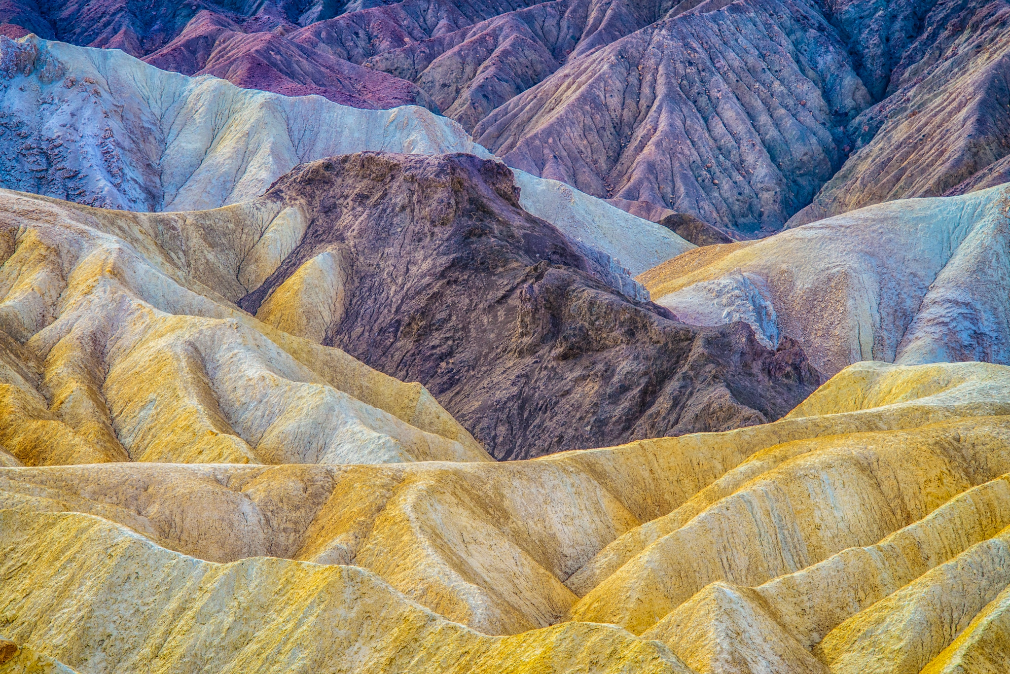This is a close-up view of the margin between the yellow Furnace Creek Formation and the multi-colored Artist's Drive formation visible from Zabriskie Point Overlook, which is accessible from Highway 190 in Death Valley National Park.