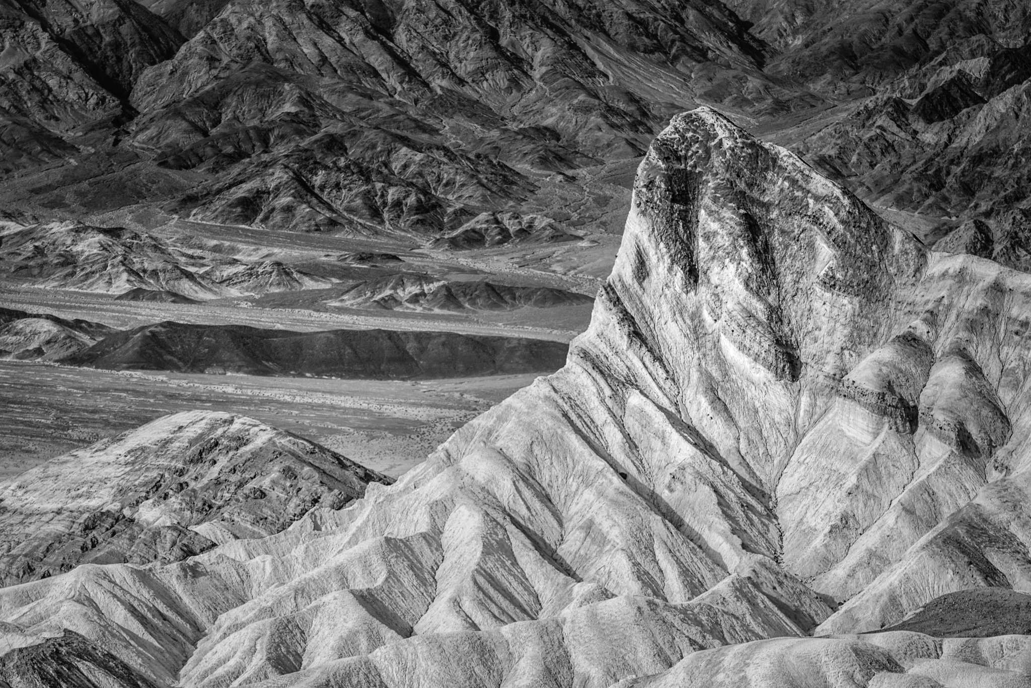 This black-and-white photograph features Manly Beacon. This viewpoint is accessible from the Zabriskie Point Overlook, which is accessible from Highway 190 in Death Valley National Park.