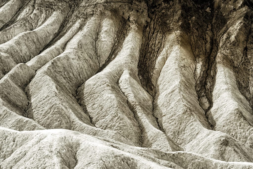 The badlands visible from the Zabriskie Point Overlook, which is accessible from Highway 190 in Death Valley National Park, are examples of dendritic drainage caused by periodic flooding.