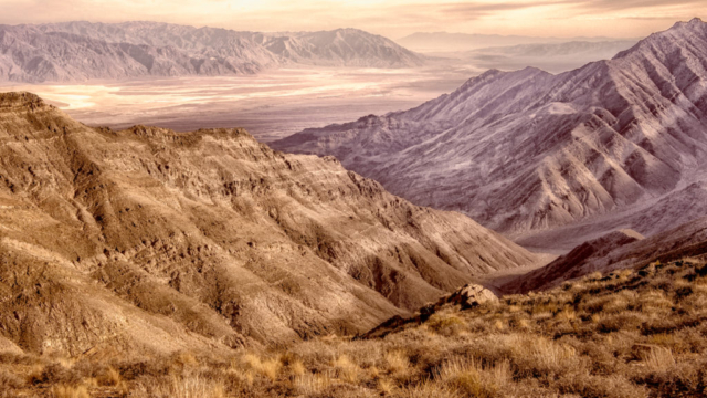 This sepia photograph shows the view from Aguereberry Point, accessible by a dirt road off Emigrant Canyon Road in Death Valley National Park, out across Death Valley and Badwater Basin to the Black Mountains to the south