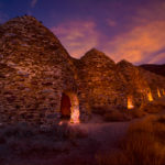 After sunset, lights illuminate the openings of the ten charcoal kilns located at the end of Wildrose Canyon in Death Valley National Park, California. This is a 2017 RMOWP awards winner.