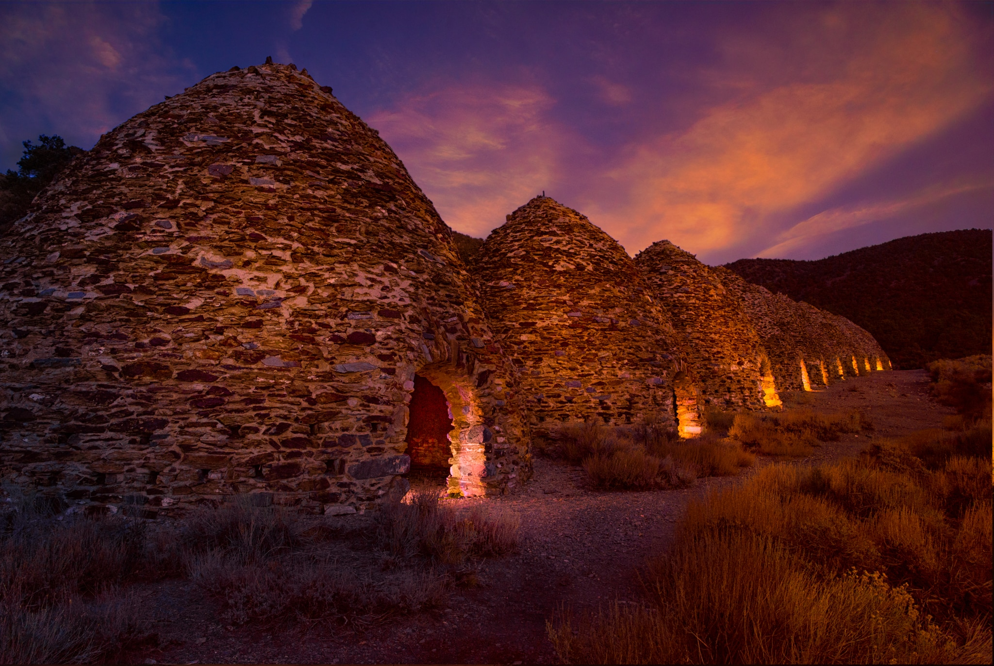 After sunset, lights illuminate the openings of the ten charcoal kilns located at the end of Wildrose Canyon in Death Valley National Park, California.