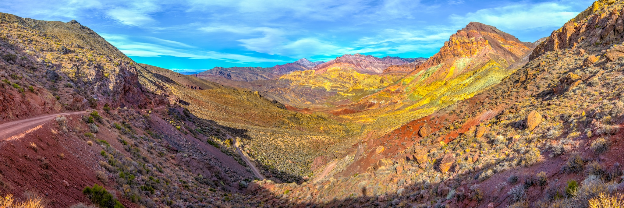From Red Pass, the the road winds down into the upper reaches of Titus Canyon. The colorful strata is the Titus Canyon Formation, which is mostly sandstone and conglomerates. The dark banded strata in the distance is the Bonanza King Formation.
