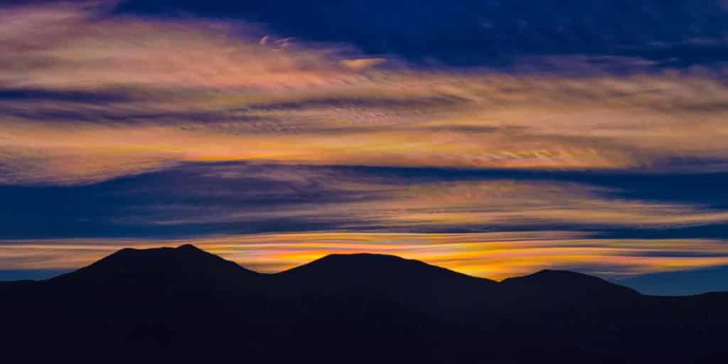 Prismatic-colored clouds glow over silhouetted mountains in Death Valley National Park. This phenomenon is called irisation.