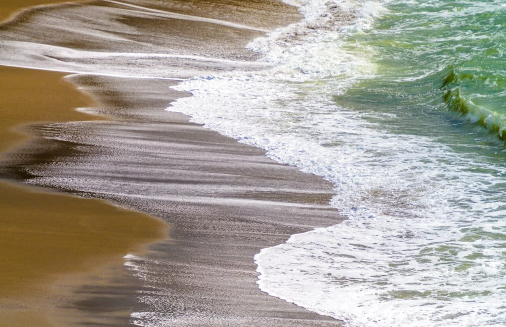 As the tide goes out, the surf creates abstract patterns on the beach at Duncan's Landing, between Bodega Bay and Jenner, California.
