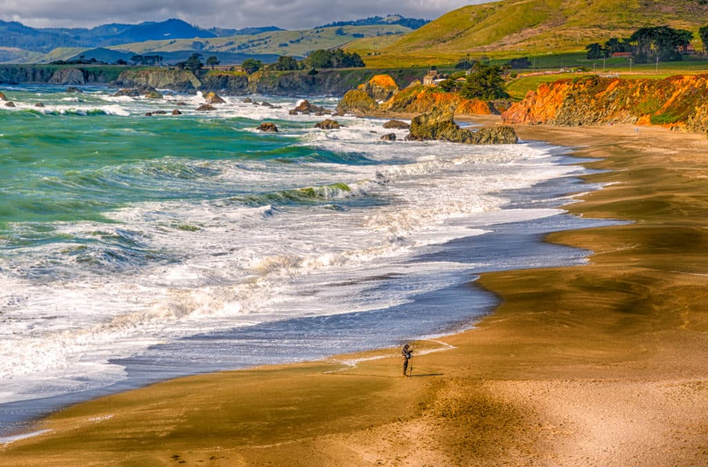 People in Nature - A fisherman enjoys an afternoon on the beach at Duncan's Landing, along CA Highway 1 in California. California's Pacific Coast