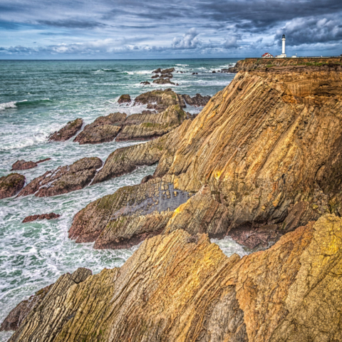 Tar sands occur interbedded with Monterey shale and shaly sandstone to create a dramatic foreground for the Point Arena Lighthouse near the Point Arena-Stornetta Unit, along California's northern coast, south of Mendocino.