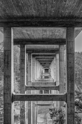 This black-and-white view of retreating squares was taken from beneath the graceful arch of the Russian Gulch Bridge, also known as the Frederick W. Panhorst Bridge, spans the Russian Gulch Creek in Russian Gulch State Park, Mendocino County, California,