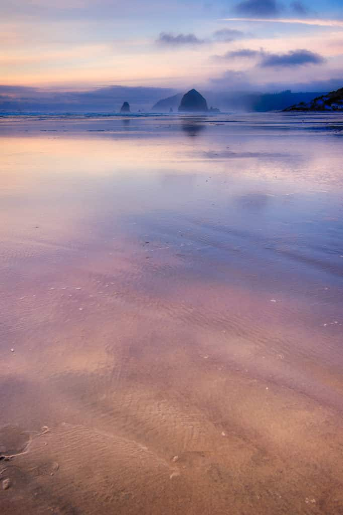 Haystack Rock is just visible in the increasing fog at sunset on Cannon Beach in Oregon