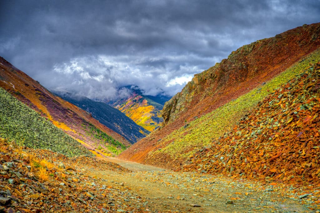A colorful view awaits as you crest Ophit Pass. Notice the green talus next to the road. Some of it is green because of mineralization and som eis green because of lichen and moss. In the distance are colorful aspen trees and scrub oaks.