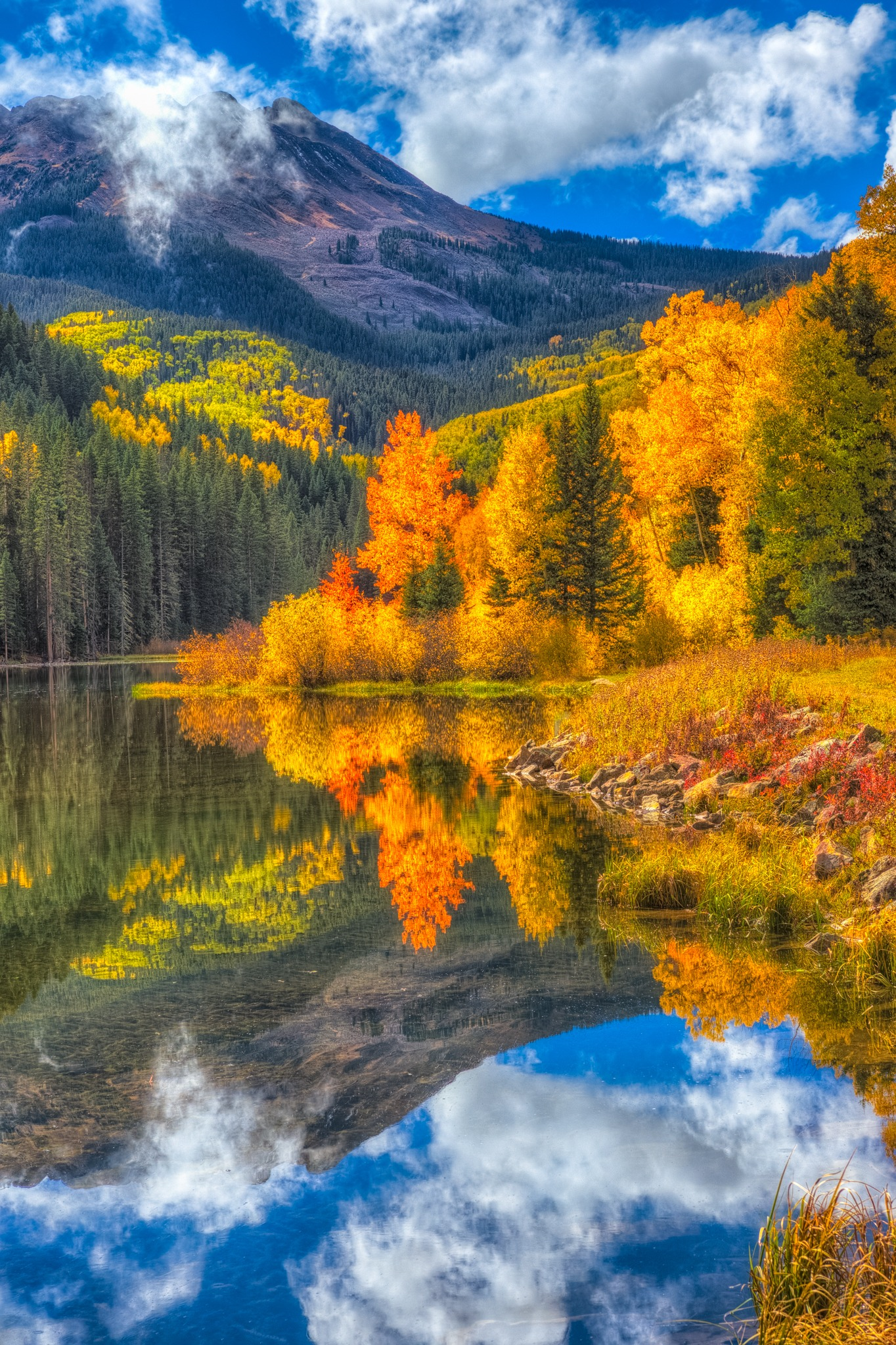Colorful aspen trees are reflected on the surface of Woods Lake, at the end of Fall Creek Road, near Telluride, Colorado.