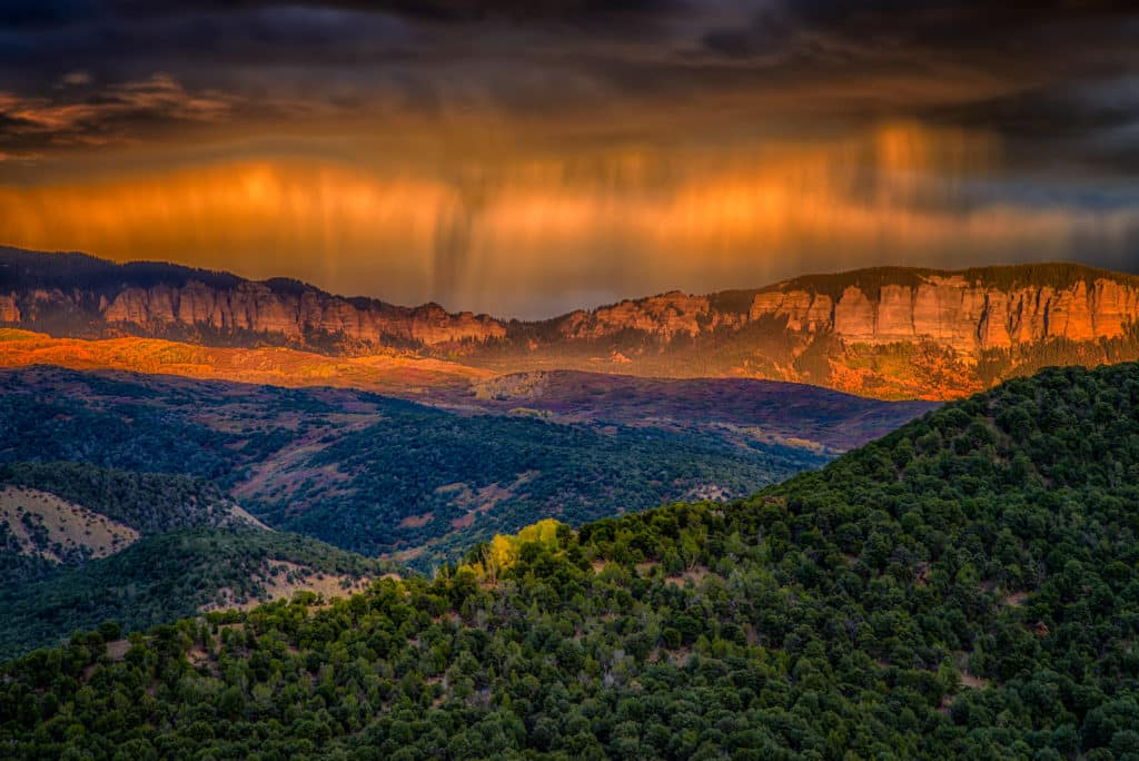 Virga over the Cimarron mountains catches the light of the setting sun, as seen from Ridgeway State Park, Colorado.