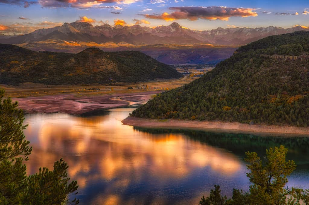Sunset colors reflect on the water remaining in the reservoir at Ridgway State Park in Ridgway, Colorado. In the distance you can see the Sneffles Range.