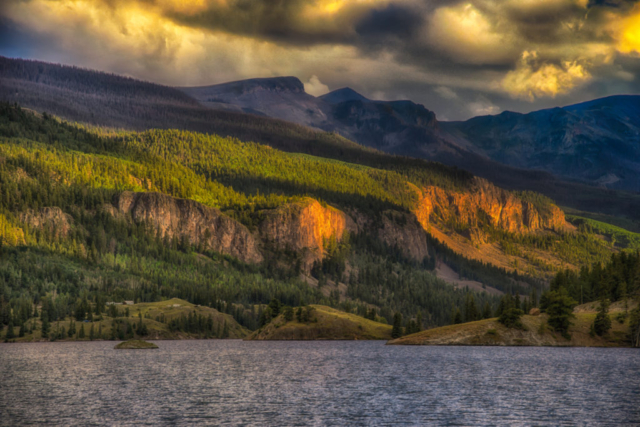 Golden light from the setting sun illuminates the rocks along the eastern shore of Lake San Cristobal near Lake City, Colorado.