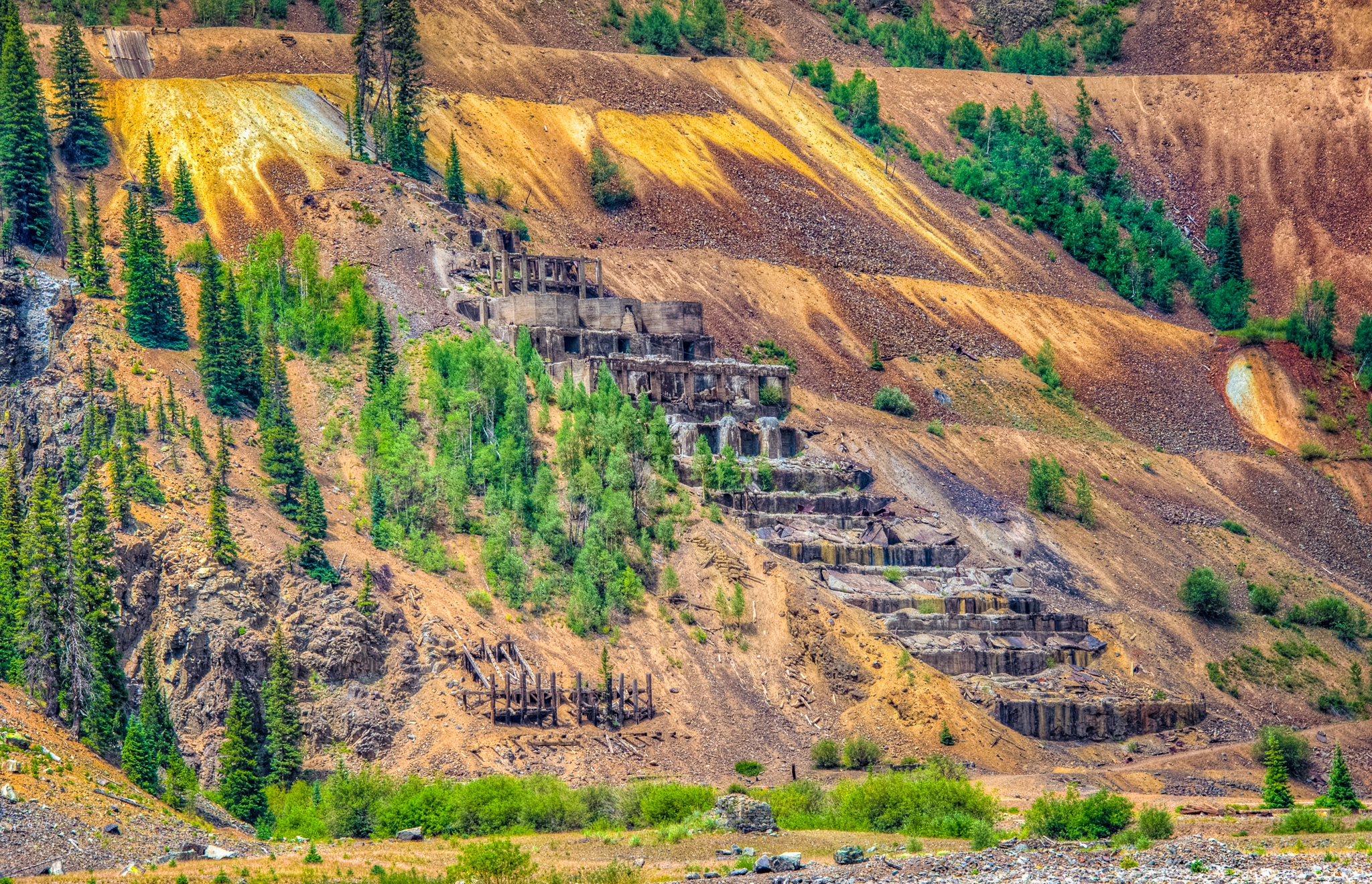 Taken from San Juan County Road 2 along the Animas River near Eureka Gulch, is a close-up view of the ruins of the Sunnyside stamping mill against a background of highly oxidized mine dump.