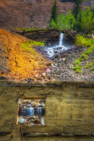 Outflow from the Old Hundred Mine creates a little cascade before emptying into Cunningham Creek, which runs along San Juan County Road 4 outside of Silverton, Colorado. Part of the Juan Mountain mining ruins collection.