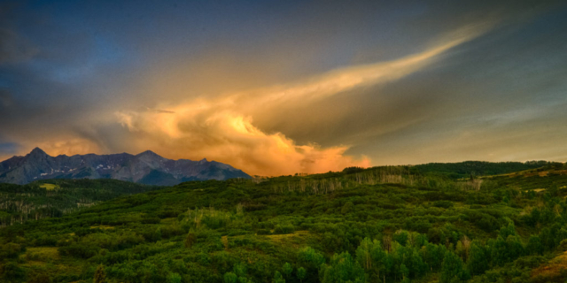The setting sun sets fire to the clouds over the Sneffles Wilderness as seen from the Dallas Divide on Highway 62 near Ridgway, Colorado.