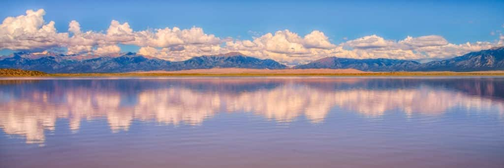 Sand Dunes National Park can be seen across San Luis Lake in San Luis State Park near Hooper, Colorado.