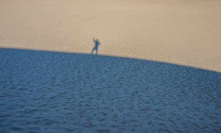 A hiker celebrates reaching the top of the dunes in Great Sand Dunes National Park and Preseve near Alamosa, Colorao.