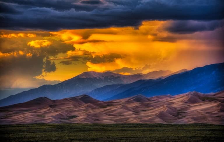 Sunsets are dramatic and colorful when competing with storm clouds at Great Sand Dunes National Park and Preserve near Alamosa, Colorado.