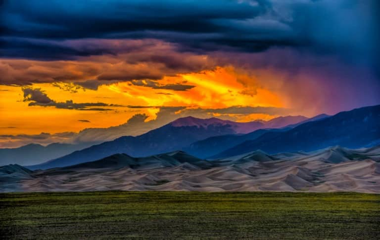 Sunsets are dramatic and colorful when competing with storm clouds at Great Sand Dunes National Park and Preserve near Alamosa, Colorado