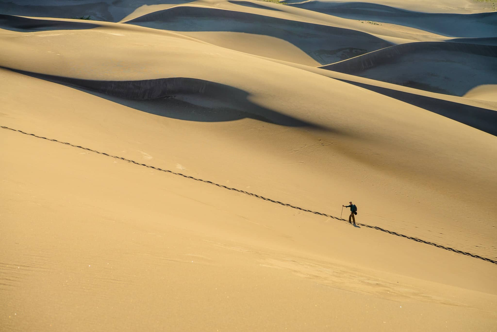 A distant hiker stops for a breather while following a trail up to the top of the first ridge of dunes in Great Sand Dunes National Park and Preserve, near Alamosa, Colorado.