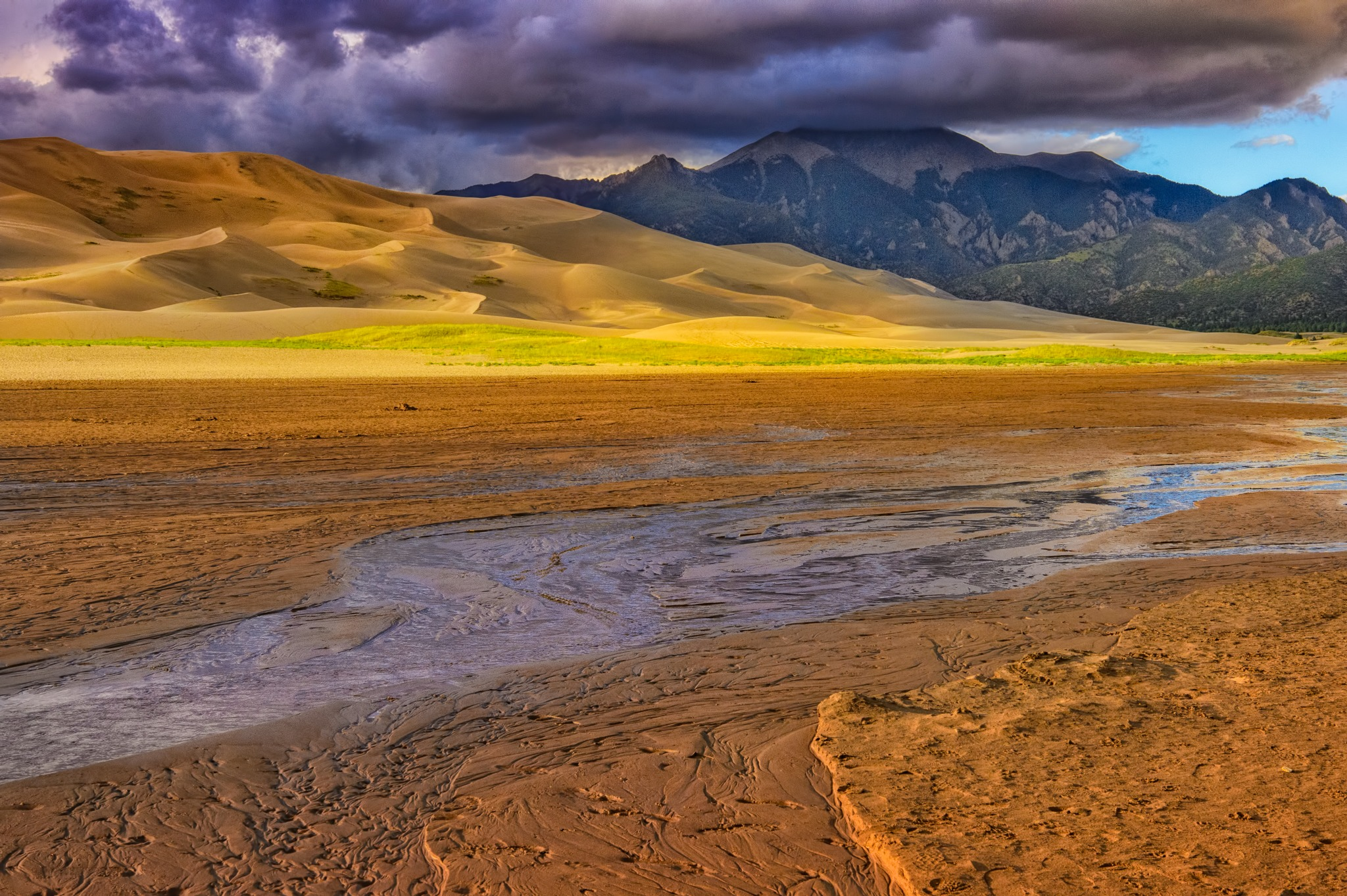 Golden afternoon light manages to sneak under the looming cloud cover of a retreating storm in Great Sand Dunes National Park and Preserve near Alamosa, Colorado.