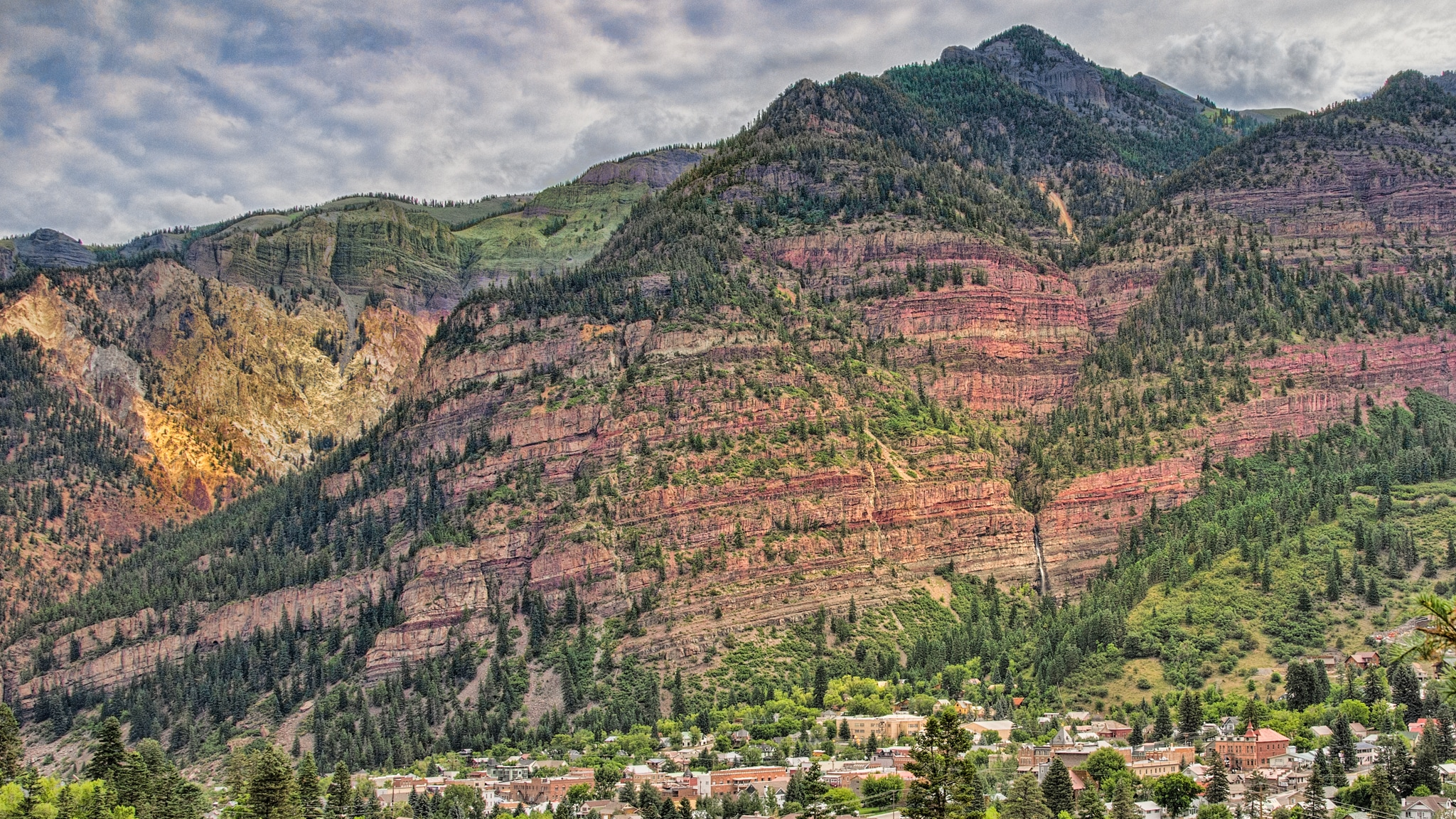 Cascade Falls is visible in the lower-right portion of the frame, above the mountain town of Ouray, Colorado.