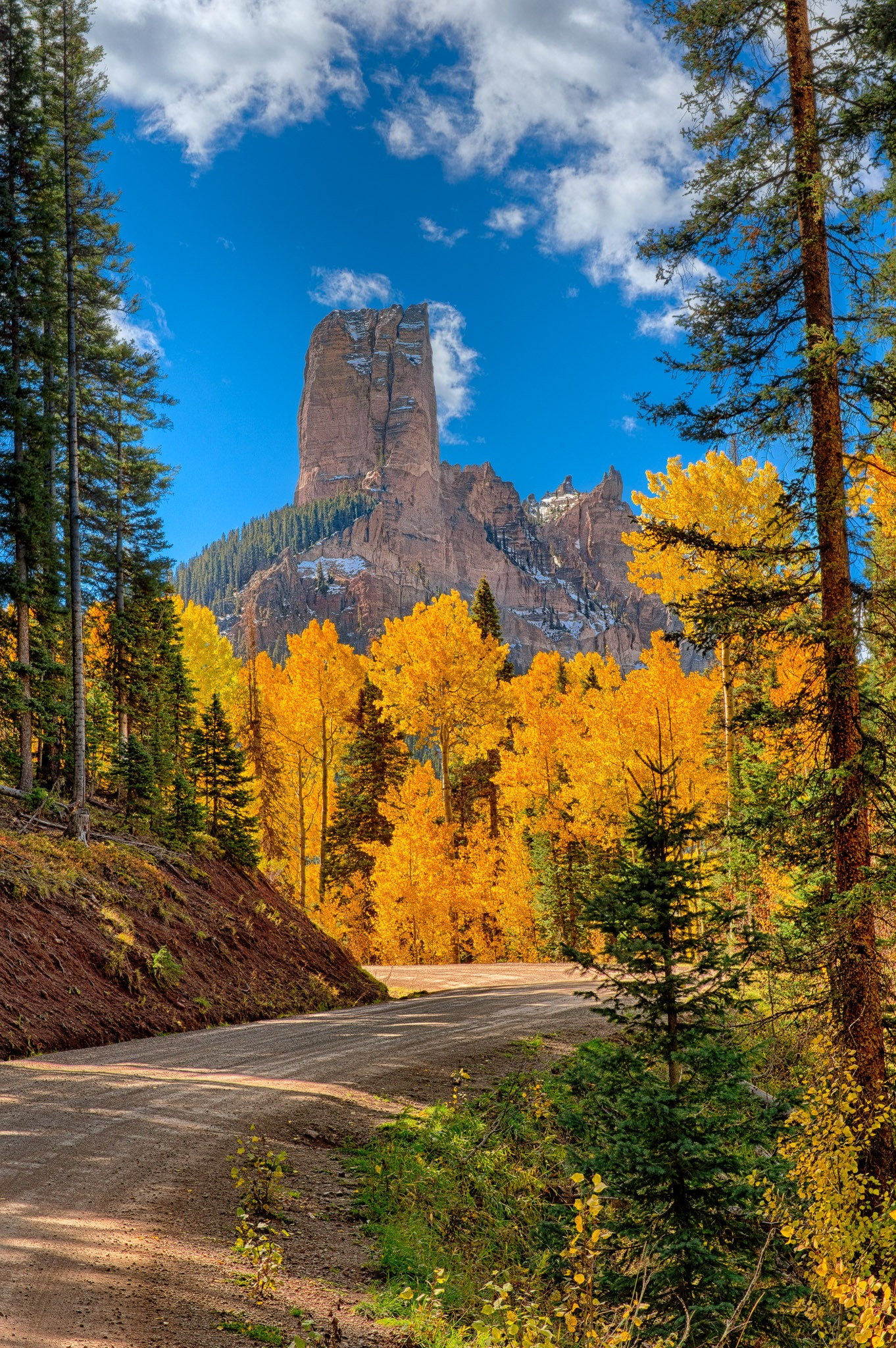 Morning light and golden aspens highlight the view of Courthouse Rock as seen from the Owl Creek Pass Road between Ridgway and Cimarron, Colorado.