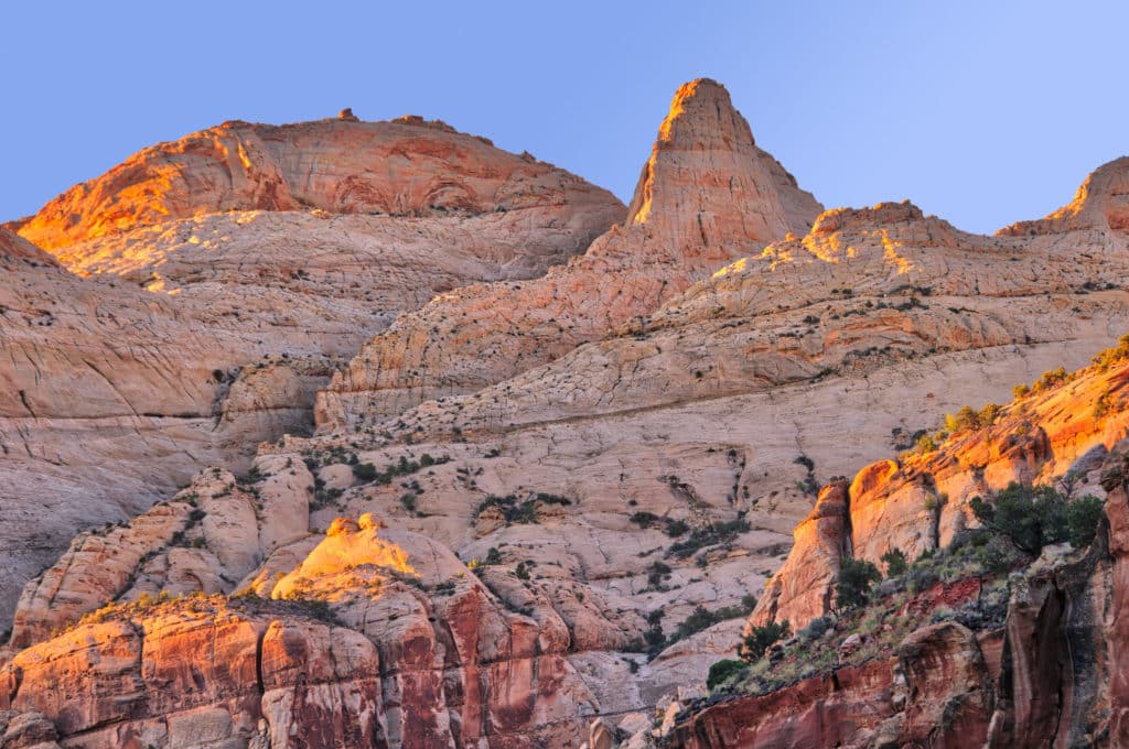Dawn sunshine lights the canyon rims along Utah Highway 24 near Capitol Dome in Capitol Reef National Park.