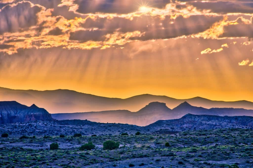 Crepuscular rays break through clouds along Caineville Wash Road near Capitol Reef National Park.