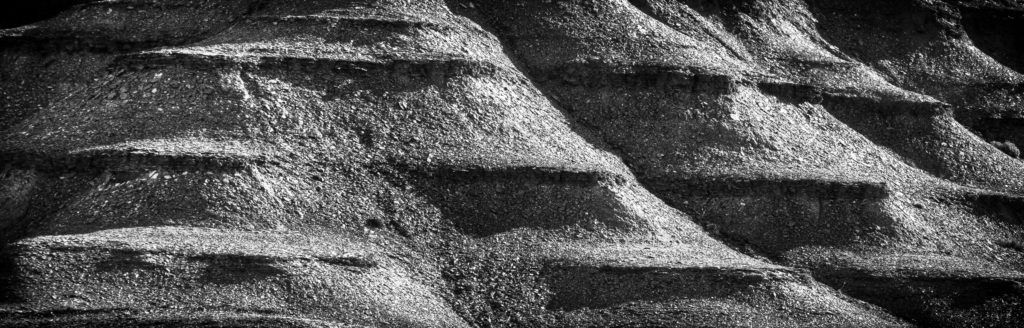 Alternating layers of sandstone and shale form ledges in cliffs above Utah Highway 24 in Capitol Reef National Park.