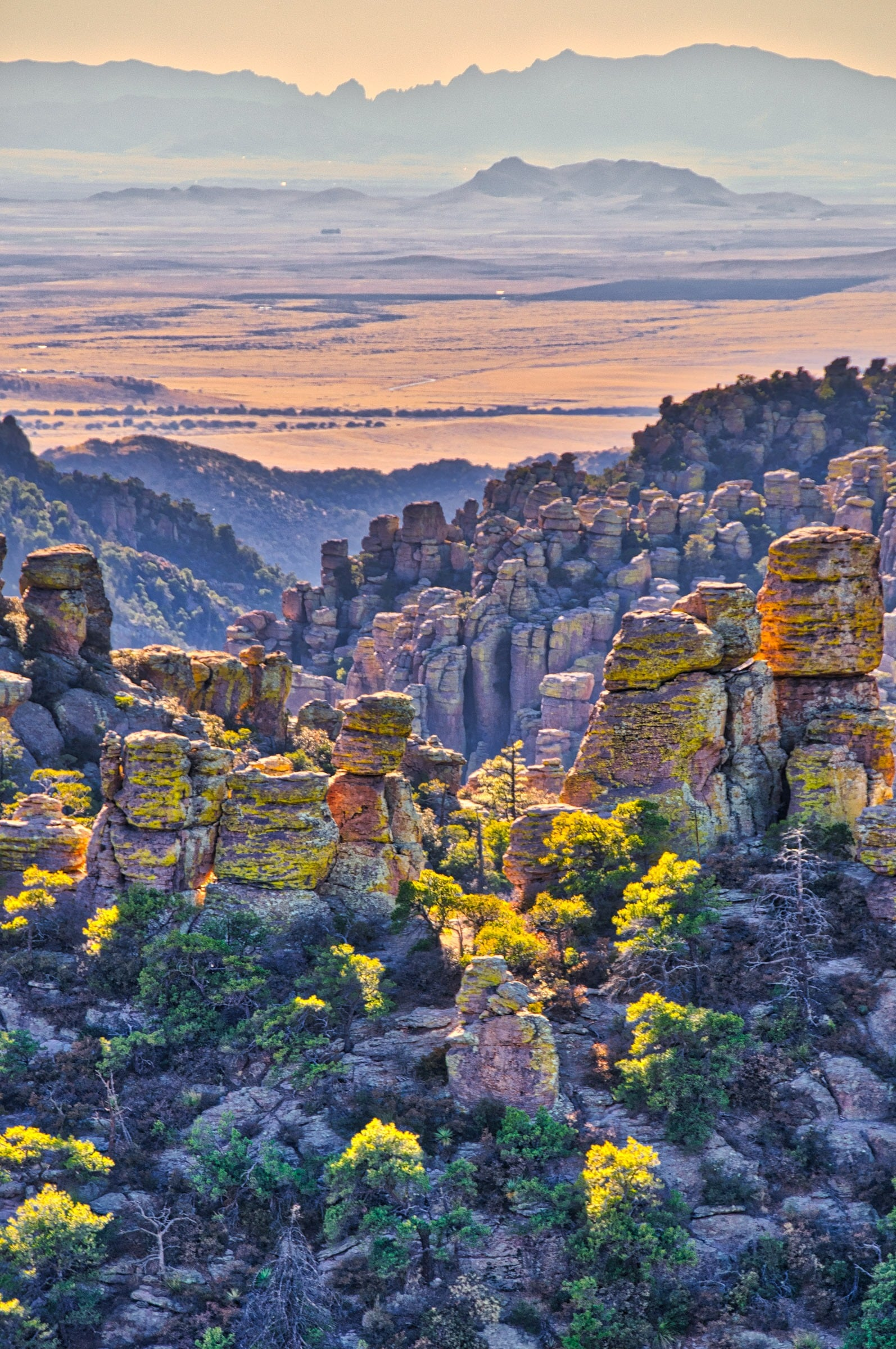 Sunset light illuminates the sides of rhyolite pinnacles, as well as the vallies beyon, in Chiricahua National Monument in Arizona.