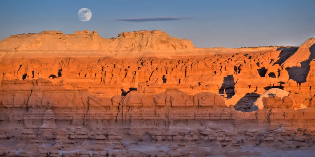 The full moon rises over Goblin Valley State Park at sunset.