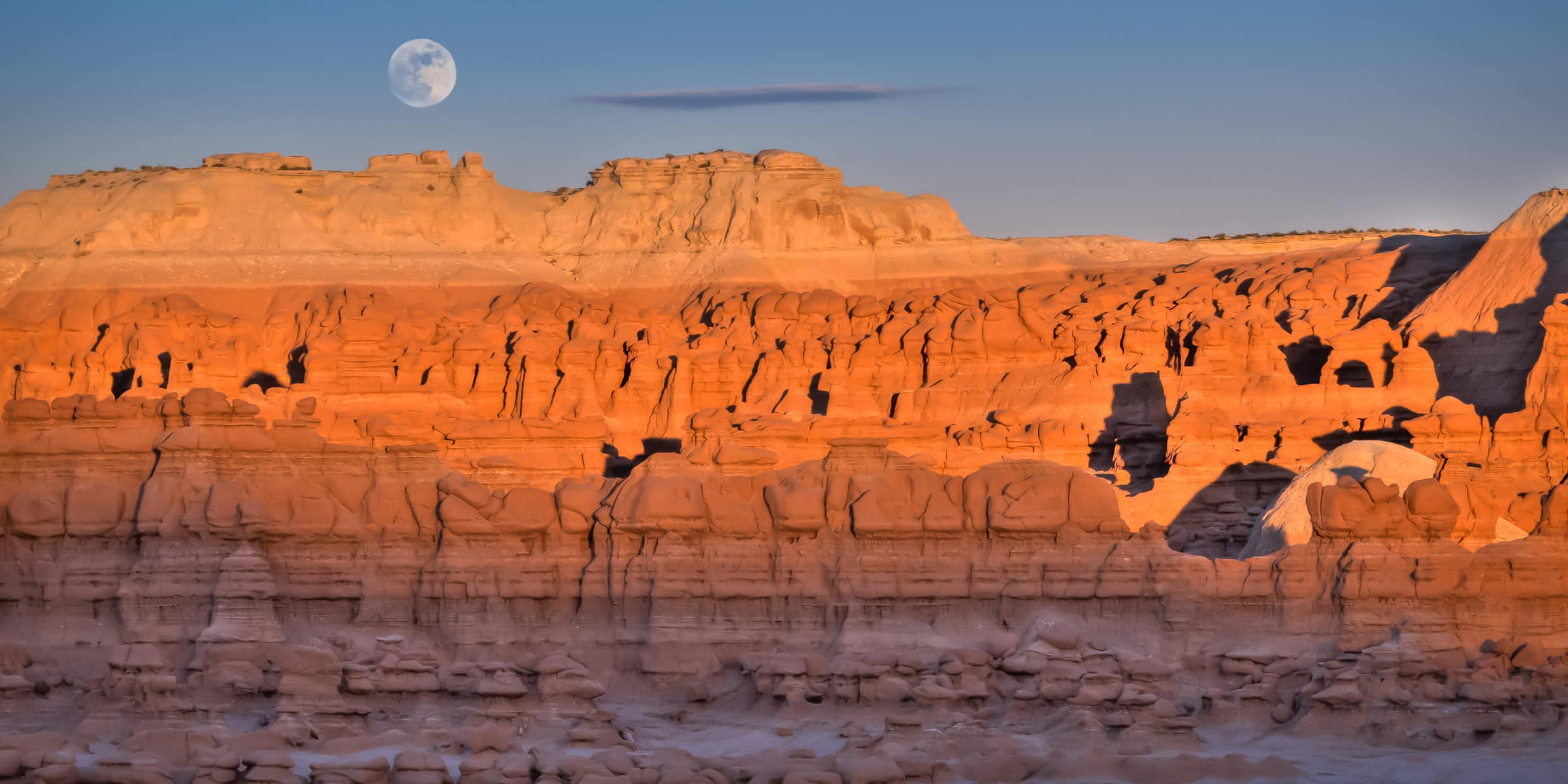 The Full Moon Rises Over Goblin Valley State Park At Sunset