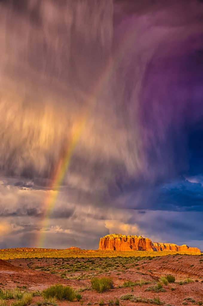 The virga from a passing thunderstorm doesn't touch the ground, but the rainbow seems to, in Goblin Valley Sate Park near Hanksville, Utah.